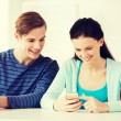 Two smiling students with smartphone at school — Stock Photo #59314635