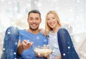 Smiling couple watching tv at home — Stock Photo