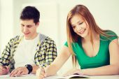 Smiling students with textbooks at school — Stock Photo