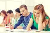 Tired students with textbooks and books at school — Stock Photo