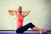 Smiling woman doing exercises on mat in gym — Stock Photo