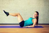 Leende kvinna gör övningar på matta i gym — Stockfoto