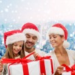 Happy family in santa helper hats with gift boxes — Stock Photo #59321027