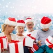 Happy family in santa helper hats with gift boxes — Stock Photo #59321069