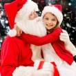 Smiling little girl with santa claus and gifts — Stock Photo #59322341
