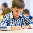 Group of school kids writing test in classroom — Stock Photo #59323135
