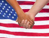 Close up of hands holding over american flag — Stock Photo