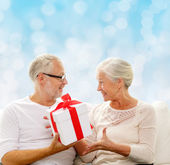 Happy senior couple with gift box at home — Stock Photo