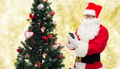 Santa claus with smartphone and christmas tree — Foto Stock