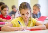 Group of school kids writing test in classroom — Stock Photo