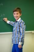 Little smiling schoolboy writing on chalk board — Stockfoto