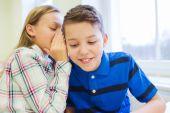 Smiling schoolgirl whispering to classmate ear — Stock Photo