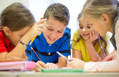 Group of students talking and writing at school — Stock Photo