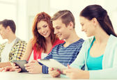 Smiling students with tablet pc at school — Stock Photo