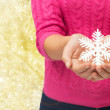 Close up of woman holding snowflake decoration — Stock Photo #59387979