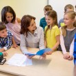 Group of school kids with teacher in classroom — Stock Photo #59388355
