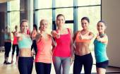 Group of women showing thumbs up gesture in gym — Stock Photo