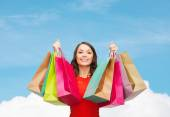 Smiling woman with colorful shopping bags — Stock Photo