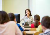 Group of school kids raising hands in classroom — Stock Photo
