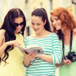 Smiling teenage girls with city guide and camera — Stock Photo #59437117