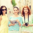 Smiling teenage girls with city guide and camera — Stock Photo #59437143