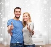 Happy couple showing thumbs up and hugging — Stock Photo