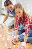 Smiling couple measuring wood flooring — Foto de Stock
