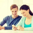 Two smiling students with smartphone at school — Stock Photo #59479259