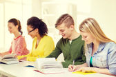 Students with textbooks and books at school — Stock Photo