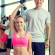 Smiling young woman with personal trainer in gym — Stock Photo #59482379