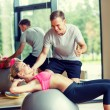 Smiling young woman with personal trainer in gym — Stock Photo #59482391
