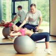 Smiling young woman with personal trainer in gym — Stock Photo #59482427