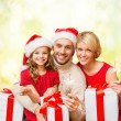 Smiling family holding gift boxes and sparkles — Stock Photo #59486487