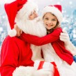Smiling little girl with santa claus and gifts — Stock Photo #59487741