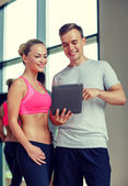 Smiling young woman with personal trainer in gym — 图库照片