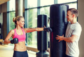 Smiling woman with personal trainer boxing in gym — Foto Stock