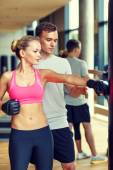 Smiling woman with personal trainer boxing in gym — Foto de Stock