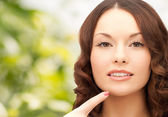 Beautiful young woman pointing finger to her chin — Stock Photo