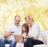 Happy family with tablet pc and credit card — Stock Photo