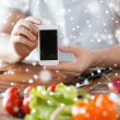 Closeup of man showing smartphone in kitchen — Stock Photo #59658677