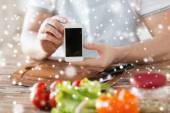 Closeup of man showing smartphone in kitchen — Stock Photo