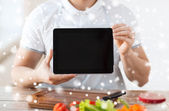 Closeup of man showing tablet pc screen in kitchen — Stock Photo