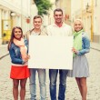 Group of smiling friends with blank white board — Stock Photo #59664237