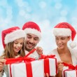 Happy family in santa hats sitting with gift boxes — Foto Stock #59667983