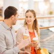 Happy couple with shopping bags drinking coffee — Stock Photo #59669297