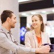 Happy couple with shopping bags drinking coffee — Stock Photo #59669315