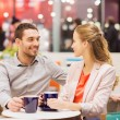 Happy couple with shopping bags drinking coffee — Stock Photo #59669321