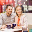 Happy couple with shopping bags drinking coffee — Stock Photo #59669343