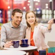 Happy couple with shopping bags drinking coffee — Stock Photo #59669359