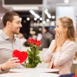 Happy couple with present and flowers in mall — Stock Photo #59669453